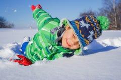 Junge, der im Schnee plaing ist Lizenzfreie Stockfotos
