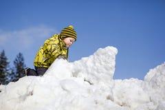 Junge, der im Schnee spielt Lizenzfreies Stockfoto