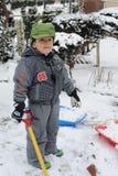 Junge, der im Schnee spielt Lizenzfreie Stockfotografie