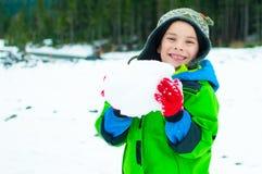 Junge, der im Schnee spielt Stockbilder