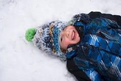 Junge, der im Schneeengel spielt Stockfoto