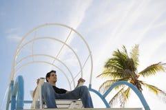 Junge, der im Strandstuhl sitzt lizenzfreies stockfoto