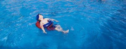 Junge, der im Swimmingpool sich entspannt Lizenzfreies Stockfoto