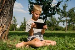 Junge, der im Tablette PC spielt lizenzfreie stockfotos