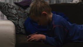 Junge, der im Telefon beim Lügen auf der Couch spielt stock video footage