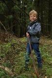 Junge, der im Wald mit hölzernem Stock blinkt Stockfoto