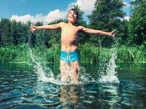 Junge, der im Wasser im Sommer spritzt Lizenzfreie Stockfotos