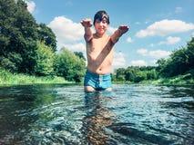 Junge, der im Wasser im Sommer spritzt Stockbild