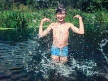 Junge, der im Wasser im Sommer spritzt Stockfotografie