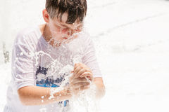 Junge, der im Wasser spielt stockfotografie