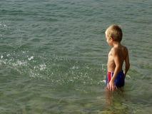 Junge, der im Wasser steht Lizenzfreies Stockfoto