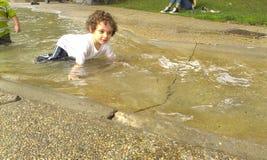 Junge, der im Wasserfluß spielt Stockbild