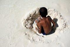 Junge, der im weißen Sand spielt Stockfotos