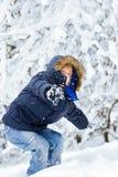 Junge, der im Winterpark spielt stockfotografie