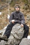 Junge, der Imbiß auf großem Stein isst Stockbilder