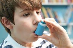 Junge, der Inhalator verwendet, um Asthmaanfall zu behandeln lizenzfreies stockfoto