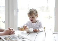 Junge, der Jogurt am Tisch isst Stockbild