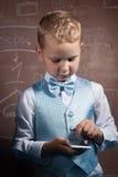 Junge in der Klage auf dem Hintergrund der Schulbehörde, Stockbilder