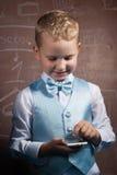 Junge in der Klage auf dem Hintergrund der Schulbehörde, Stockfotografie