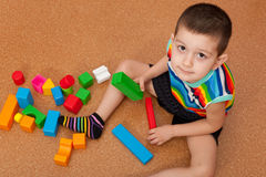 Junge, der klare Spielzeugblöcke spielt Stockfotografie