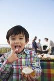 Junge, der kleinen Kuchen, Finger in seinem Mund isst und Kamera betrachtet stockfotografie