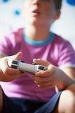 Junge, der Kontrolleur Playing Video Game hält stockfoto