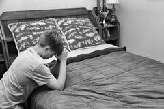Junge, der am Kopfende betet stockfoto