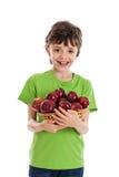 Junge, der Korb der roten Äpfel getrennt auf Weiß anhält Lizenzfreie Stockfotos