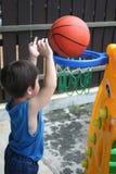 Junge, der Korbkugel spielt Lizenzfreie Stockbilder