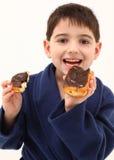 Junge, der Krapfen isst Stockfotos