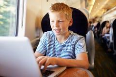Junge, der Laptop auf Zug-Reise verwendet lizenzfreie stockfotos