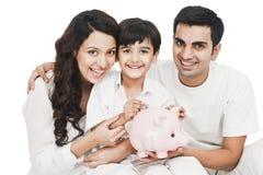 Junge, der Münze in ein Sparschwein mit seinem Elternlächeln einsetzt Lizenzfreies Stockbild
