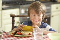 Junge, der Mahlzeit in der Küche isst stockfotografie