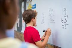 Junge, der mathematisches Problem löst Stockbild