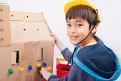 Junge, der Mechanikergebäude-Papierhaus spielt Lizenzfreie Stockbilder
