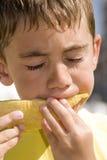 Junge, der Melone isst Stockbild