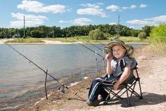 Junge, der mit Angeln auf der Bank des Teichs sitzt Lizenzfreies Stockbild