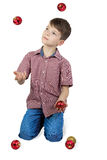 Junge, der mit Christbaumkugeln jongliert Lizenzfreie Stockfotografie