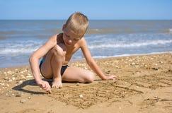 Junge, der mit dem Sand auf dem Strand spielt Lizenzfreies Stockfoto