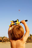 Junge, der mit Drachen am Strand spielt Lizenzfreie Stockfotografie