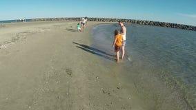 Junge, der mit einem Ball auf dem Strand spielt stock video