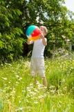 Junge, der mit einem Ball auf einer üppigen Wiese spielt Stockbilder