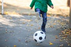 Junge, der mit einem Ball im Herbst auf der Straße spielt Stockfotos