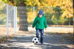 Junge, der mit einem Ball im Herbst auf der Straße spielt Lizenzfreies Stockbild