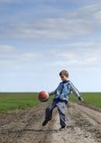 Junge, der mit einem Ball spielt Lizenzfreies Stockbild