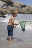 Junge, der mit einem Fischernetz spielt. Lizenzfreies Stockbild