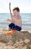 Junge, der mit einem großen Stock gräbt lizenzfreies stockfoto