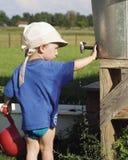 Junge, der mit einem Hahn spielt Stockfotografie