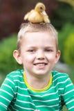 Junge, der mit einem kleinen Entlein spielt Ducken Sie das Sitzen auf dem Kopf des Kindes lizenzfreie stockbilder