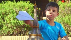 Junge, der mit einem Papierflugzeug spielt stock video footage
